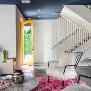 Diseño de puerta principal urbana, de tamaño medio, con paredes azules, suelo de cemento, puerta simple, puerta naranja y suelo gris