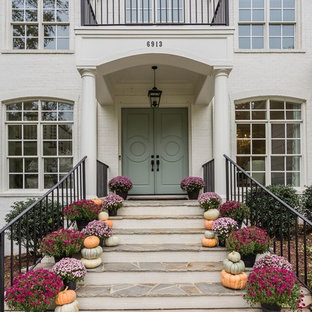 Inspiration for a transitional entryway remodel in Raleigh with white walls and a green front door