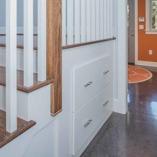 Esempio di un ingresso con anticamera chic di medie dimensioni con pareti arancioni, pavimento in cemento, una porta singola, una porta grigia e pavimento grigio