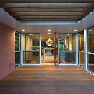 アトランタの回転式ドアおしゃれな玄関ドア (ピンクの壁、濃色木目調のドア) の写真