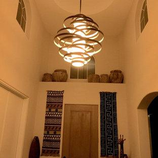 Réalisation d'un hall d'entrée bohème de taille moyenne avec un sol en carrelage de porcelaine, une porte simple, une porte en bois brun, un sol gris et un mur blanc.