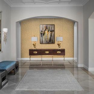 Idée de décoration pour un très grand hall d'entrée design avec un sol en marbre, une porte double, une porte en bois foncé et un sol beige.