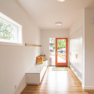 Mittelgroßer Moderner Eingang mit Foyer, weißer Wandfarbe, braunem Holzboden, Einzeltür, orangefarbener Tür und braunem Boden in Seattle