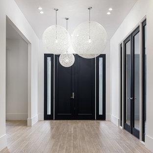 ニューヨークの広い両開きドアコンテンポラリースタイルのおしゃれな玄関ロビー (白い壁、淡色無垢フローリング、黒いドア、茶色い床) の写真