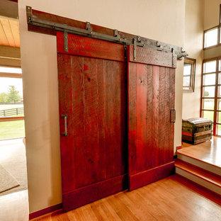 Cette image montre un petit hall d'entrée design avec un mur beige, un sol en bois clair, une porte double, une porte rouge et un sol beige.
