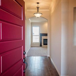 Idee per un corridoio classico di medie dimensioni con pareti beige, pavimento in legno massello medio, una porta singola, una porta bianca e pavimento rosso