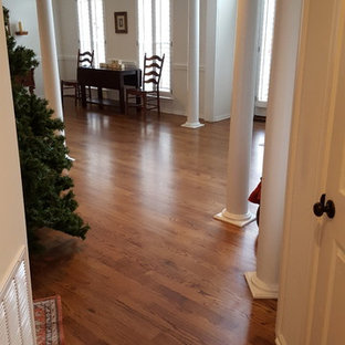 Large minimalist dark wood floor and brown floor entryway photo in Charlotte with white walls and a white front door
