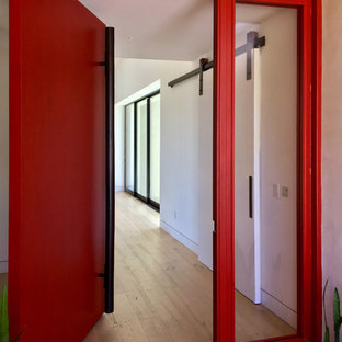Large minimalist light wood floor and beige floor entryway photo with white walls and a red front door