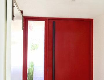 Red Steel Pivot Door on a Modern Masterpiece in La Costa