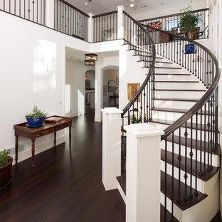 Modelo de puerta principal tradicional, extra grande, con paredes blancas, suelo de madera oscura, puerta simple, puerta blanca y suelo marrón