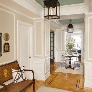 Bild på en mellanstor vintage foajé, med beige väggar, mellanmörkt trägolv, en pivotdörr, en svart dörr och brunt golv