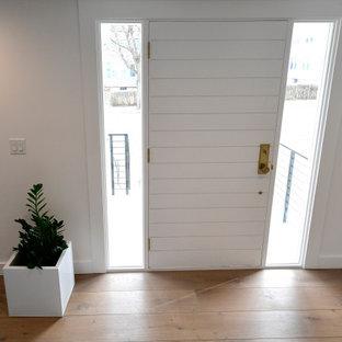 Modern inredning av en stor foajé, med vita väggar, ljust trägolv, en enkeldörr och vitt golv