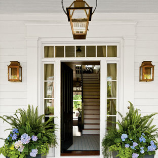 Cette image montre une porte d'entrée rustique avec une porte noire et une porte simple.