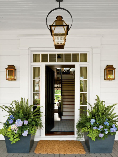 example of a country front door design in atlanta with a black front door and a