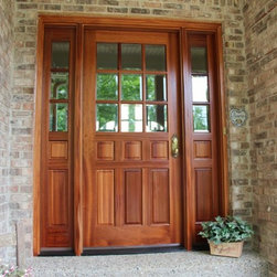Replacement Entry Doors - Wood entry door with sidelights and windows containing rectangular grilles.