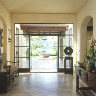 Foyer - mediterranean foyer idea in San Diego with beige walls