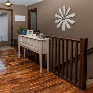 Exempel på en lantlig entré, med bruna väggar, mörkt trägolv, en enkeldörr, en brun dörr och brunt golv