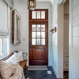 На фото: вестибюль в стиле кантри с белыми стенами, полом из сланца, одностворчатой входной дверью и входной дверью из темного дерева