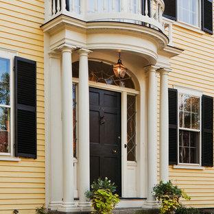 Cette image montre une grand porte d'entrée traditionnelle avec une porte simple, une porte noire et un mur jaune.