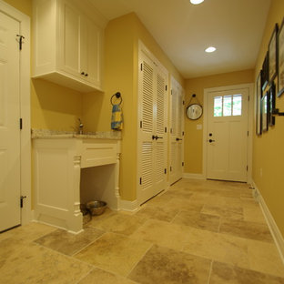 Example of a mid-sized classic travertine floor entryway design in Milwaukee with yellow walls and a white front door