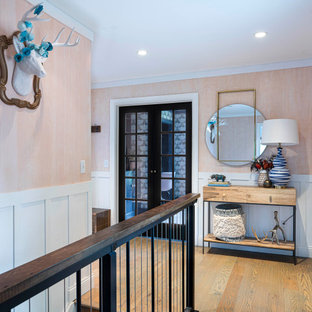 На фото: маленькая входная дверь в стиле кантри с розовыми стенами, паркетным полом среднего тона, одностворчатой входной дверью, коричневой входной дверью и коричневым полом