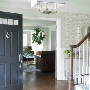 Example of a small transitional medium tone wood floor and brown floor entryway design in New York with white walls and a black front door