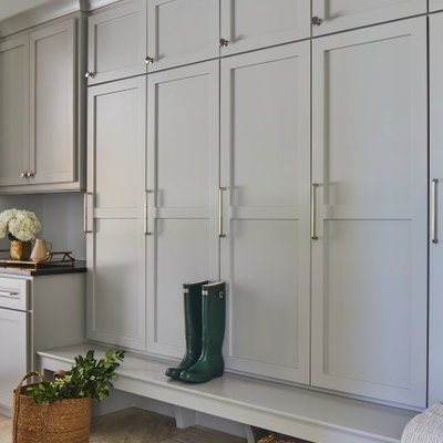 Example of a large transitional travertine floor and beige floor mudroom design in Other with white walls