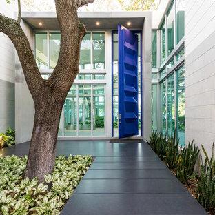 Inspiration för en stor funkis ingång och ytterdörr, med en pivotdörr, vita väggar, granitgolv och en blå dörr