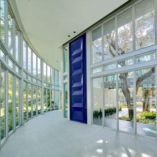 マイアミの広い回転式ドアモダンスタイルのおしゃれな玄関ドア (ライムストーンの床、青いドア) の写真
