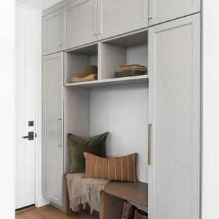 Idéer för lantliga kapprum, med vita väggar, mellanmörkt trägolv, en enkeldörr, en vit dörr och brunt golv