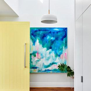Modern inredning av en foajé, med vita väggar, en gul dörr, mellanmörkt trägolv, en enkeldörr och brunt golv