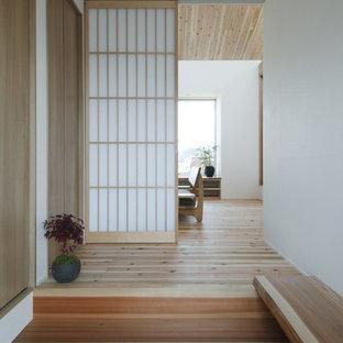 Aménagement d'une petite entrée asiatique avec un couloir, un mur blanc, un sol en bois clair, une porte simple, une porte en bois clair et un sol beige.