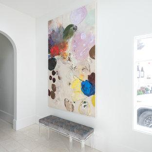 Réalisation d'une grande entrée minimaliste avec un couloir, un mur blanc, un sol en calcaire, une porte simple, une porte métallisée et un sol blanc.