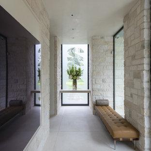 Idées déco pour un hall d'entrée moderne de taille moyenne avec un mur beige, un sol en carrelage de porcelaine, une porte pivot, une porte noire et un sol beige.