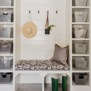 Photo of a beach style mudroom in Boston with white walls, concrete floors and grey floor.