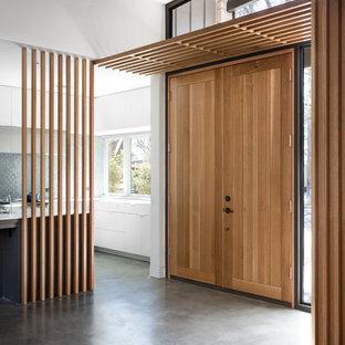 Idéer för att renovera en 60 tals foajé, med vita väggar, betonggolv, en dubbeldörr och mellanmörk trädörr