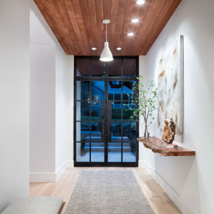オースティンの広い片開きドアコンテンポラリースタイルのおしゃれな玄関ロビー (白い壁、淡色無垢フローリング、黒いドア、茶色い床、塗装板張りの天井、塗装板張りの壁) の写真