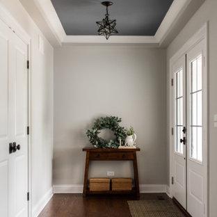 На фото: входная дверь среднего размера в стиле современная классика с темным паркетным полом, двустворчатой входной дверью, белой входной дверью, коричневым полом и многоуровневым потолком