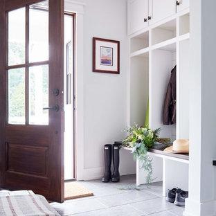 Diseño de vestíbulo posterior de estilo de casa de campo, de tamaño medio, con paredes blancas, puerta simple, puerta de madera oscura, suelo gris y suelo de baldosas de porcelana