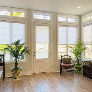 На фото: фойе в стиле фьюжн с одностворчатой входной дверью, белой входной дверью, полом из бамбука, коричневым полом и серыми стенами