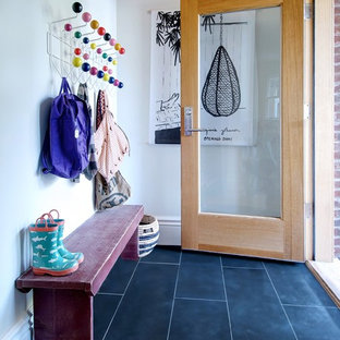 Mid-sized trendy slate floor and black floor entryway photo in Toronto with white walls and a medium wood front door