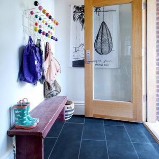 Idée de décoration pour une entrée design de taille moyenne avec un sol en ardoise, un sol noir, un vestiaire, un mur blanc, une porte simple et une porte en bois brun.