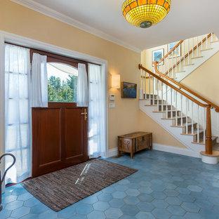 Ispirazione per una porta d'ingresso chic di medie dimensioni con pareti gialle, pavimento con piastrelle in ceramica, una porta singola, una porta in legno scuro e pavimento blu