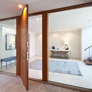 東京23区の広い片開きドアモダンスタイルのおしゃれな玄関ラウンジ (白い壁、大理石の床、木目調のドア、ベージュの床) の写真