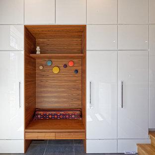 Aménagement d'une entrée rétro avec un vestiaire, un mur blanc et un sol gris.