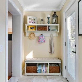 Ejemplo de vestíbulo posterior marinero, pequeño, con paredes amarillas, suelo de baldosas de porcelana, puerta simple y puerta blanca