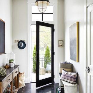 На фото: узкая прихожая в морском стиле с бежевыми стенами, одностворчатой входной дверью, стеклянной входной дверью и черным полом с