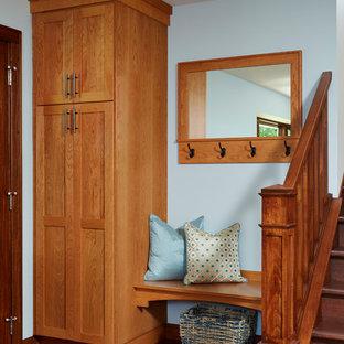 Exemple d'une entrée chic avec un vestiaire, un mur bleu et un sol en bois foncé.