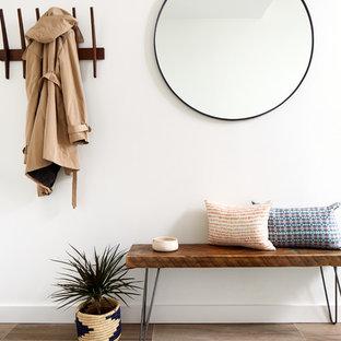 Diseño de distribuidor actual, pequeño, con paredes blancas, suelo de baldosas de porcelana y suelo marrón