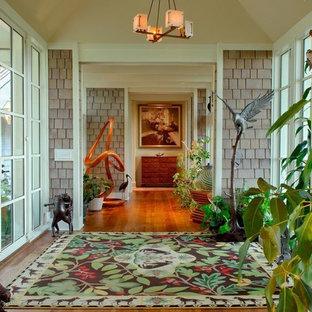 チャールストンの中くらいの両開きドアトロピカルスタイルのおしゃれな玄関ロビー (無垢フローリング、ガラスドア、グレーの壁) の写真